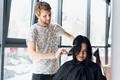 Going for a change of style. Young beautiful woman discussing hairstyling with her hairdresser while - PhotoDune Item for Sale