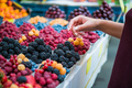 Marketplace with different fruits. Seller's hand on colorful berry background outdoors. Sale - PhotoDune Item for Sale