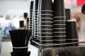 Black paper cups on a counter against the background of a blurred coffee bar at mall with takeaway - PhotoDune Item for Sale