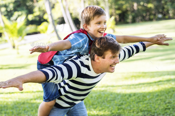 Superhero boy flying on the back of his dad - Stock Photo - Images