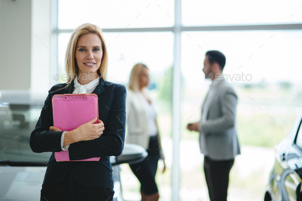 Professional saleswoman working in car dealership - Stock Photo - Images
