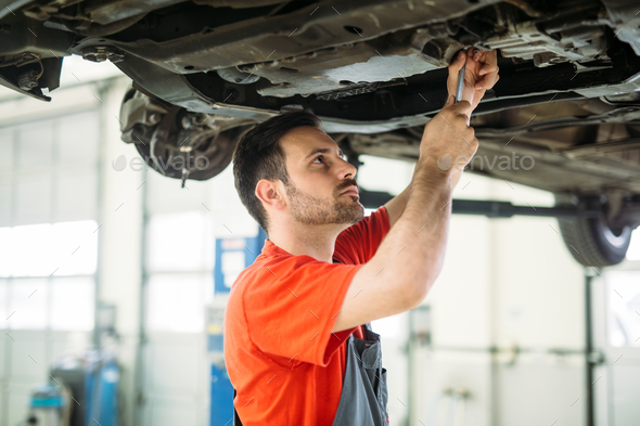 Auto mechanic working in garage. Repair service. - Stock Photo - Images