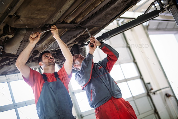 Two mechanics in uniform are working in auto service with lifted vehicle - Stock Photo - Images