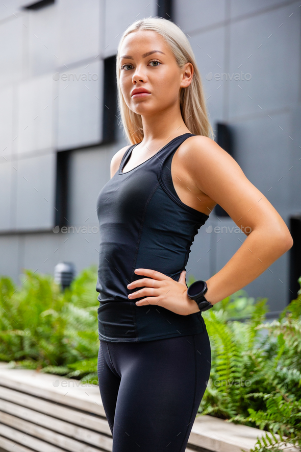 Confident Female Urban Jogger Standing With Hand On Waist - Stock Photo - Images