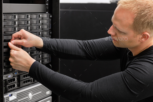 Male Technical Consultant Adjusting Hard Drives In SAN At Datace - Stock Photo - Images