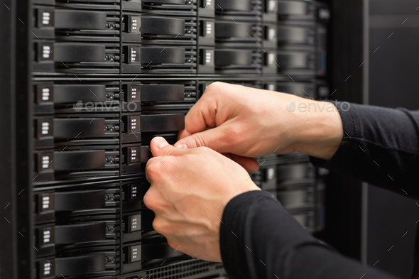 Male IT Engineer Adjusting Hard Drives In SAN At Datacenter - Stock Photo - Images