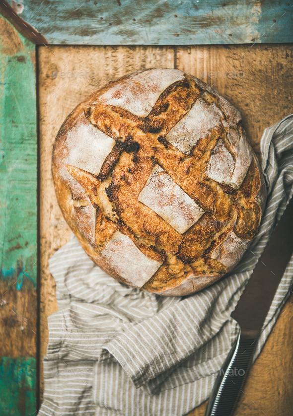 Flat-lay of sourdough wheat bread over rustic background - Stock Photo - Images