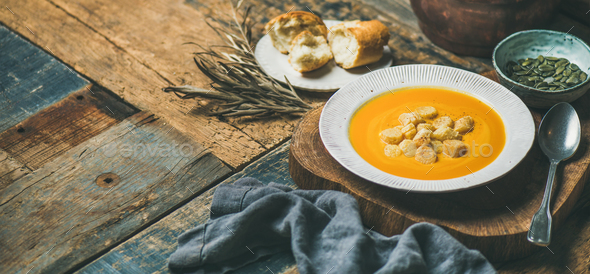 Warming pumpkin cream soup with croutons and seeds, wide composition - Stock Photo - Images