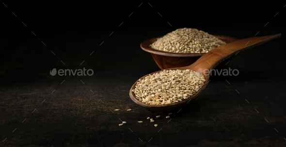 a wooden spoon and bowl of sesame seeds - Stock Photo - Images