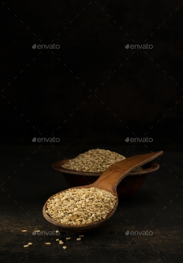 A wooden spoonful of sesame seeds - Stock Photo - Images