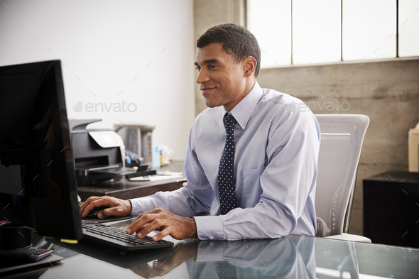Mixed race businessman using computer in an office - Stock Photo - Images