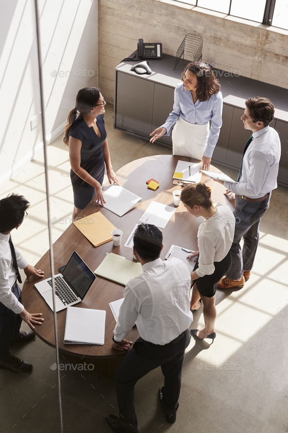 Female manager in team meeting, elevated view through window - Stock Photo - Images