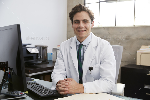 Young white male doctor at desk, portrait - Stock Photo - Images