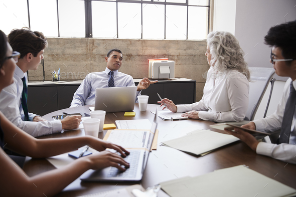 Male manager brainstorming with team in meeting room - Stock Photo - Images