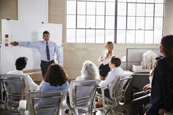 Businessmastands using whiteboard during a presentation - Stock Photo - Images