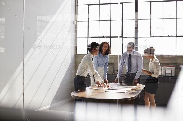 Business team seen through window working together in office - Stock Photo - Images