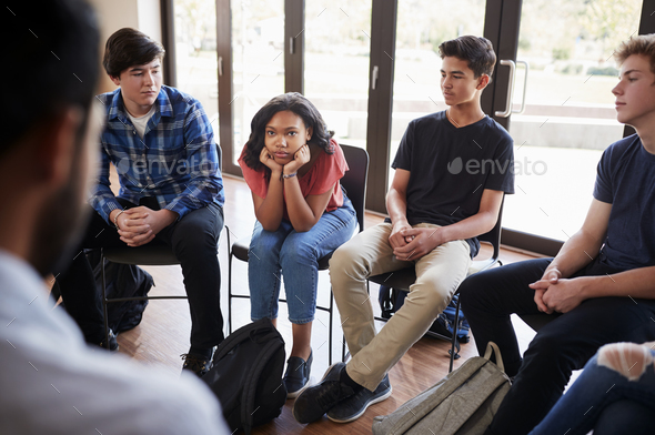 Unhappy Female Pupil In High School Discussion Group - Stock Photo - Images