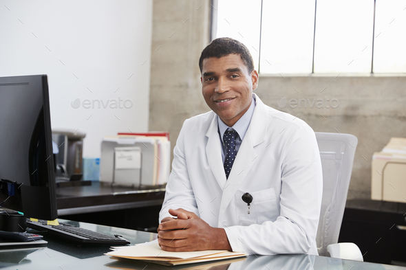 Mixed race  male doctor at desk, portrait - Stock Photo - Images
