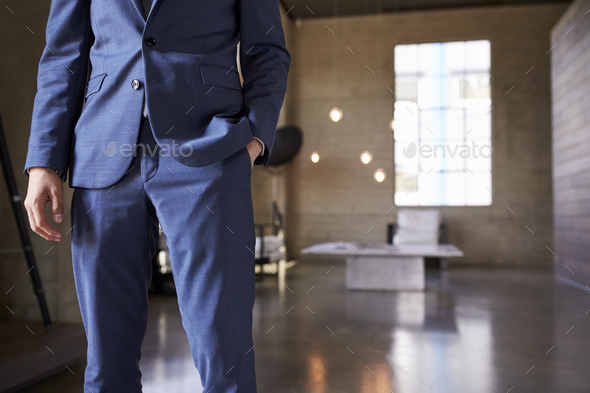 Mid section of man in blue suit standing, hand in pocket - Stock Photo - Images
