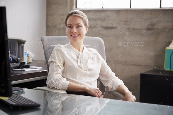 Young white woman sitting at office desk smiling to camera - Stock Photo - Images