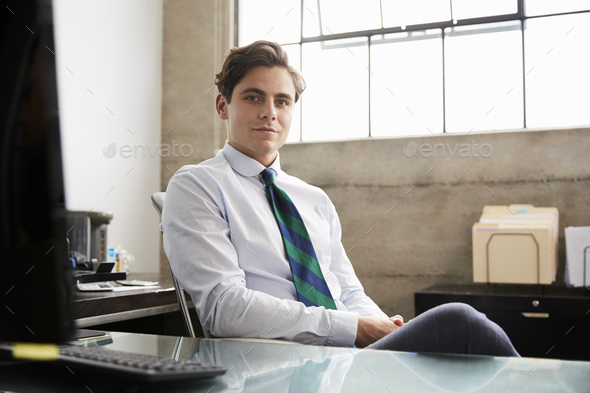 Young white businessman at an office desk looking to camera - Stock Photo - Images