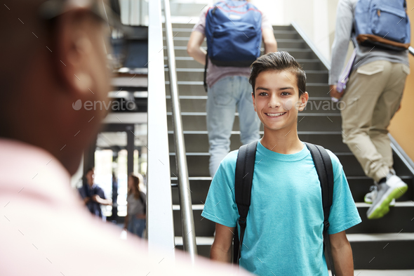 Male High School Student Talking With Teacher In Busy Corridor - Stock Photo - Images