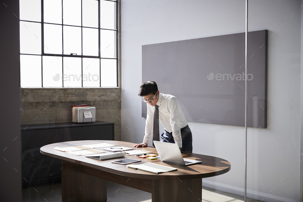 Businessman standing at desk working alone in an office - Stock Photo - Images