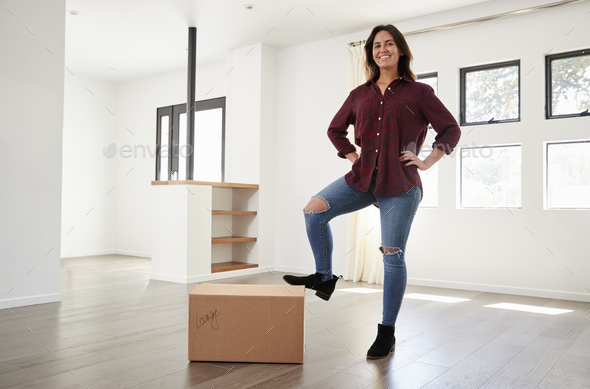 Portrait Of Proud Woman Standing On Box In New Home On Moving Day - Stock Photo - Images