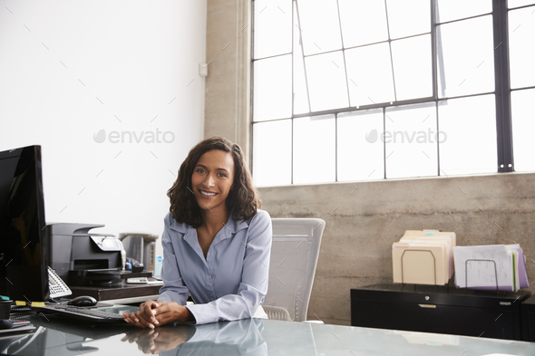 Young mixed race woman at office desk smiling to camera - Stock Photo - Images