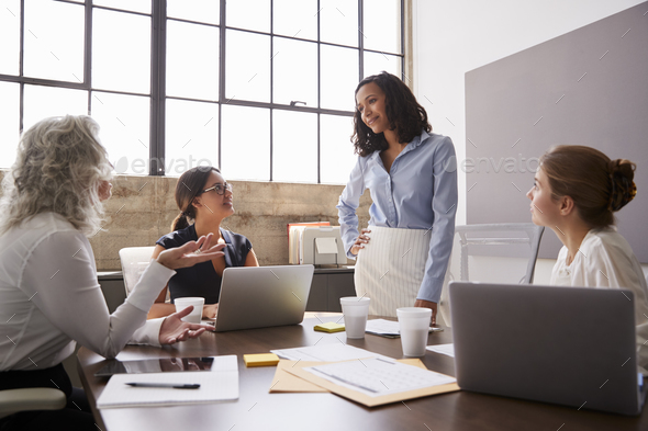 Businesswoman listening to female colleagues in a meeting - Stock Photo - Images