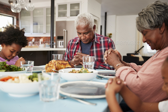 Grandparents Praying Before Meal At Home With Granddaughters - Stock Photo - Images
