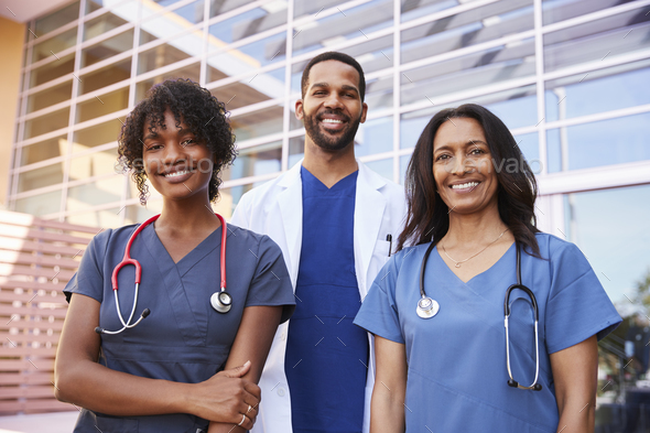 Three healthcare colleagues standing outside modern hospital - Stock Photo - Images