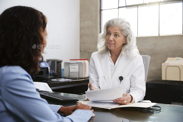 Senior female doctor in consultation with patient in office - Stock Photo - Images