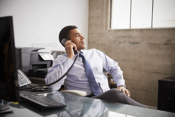 Mixed race businessman at an office desk using the phone - Stock Photo - Images