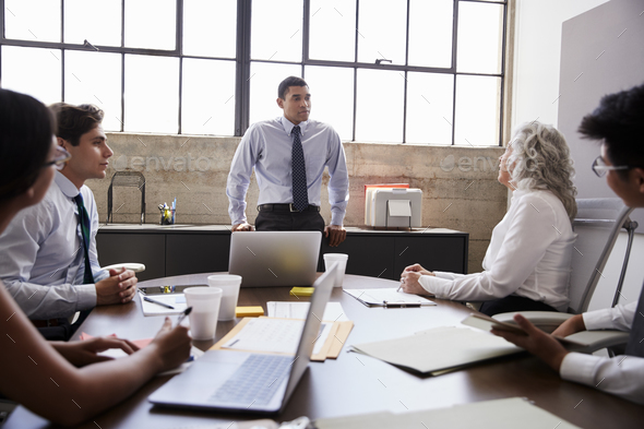 Male manager stands listening to team in brainstorm meeting - Stock Photo - Images