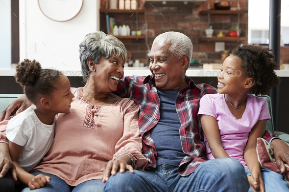 Grandparents Relaxing On Sofa At Home With Granddaughters - Stock Photo - Images