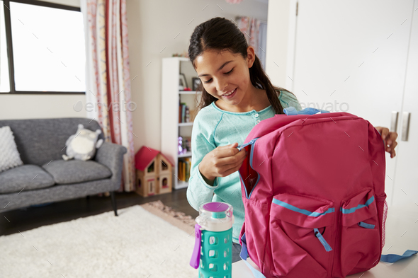 Young Girl In Bedroom Zipping Up Bag Ready For School - Stock Photo - Images