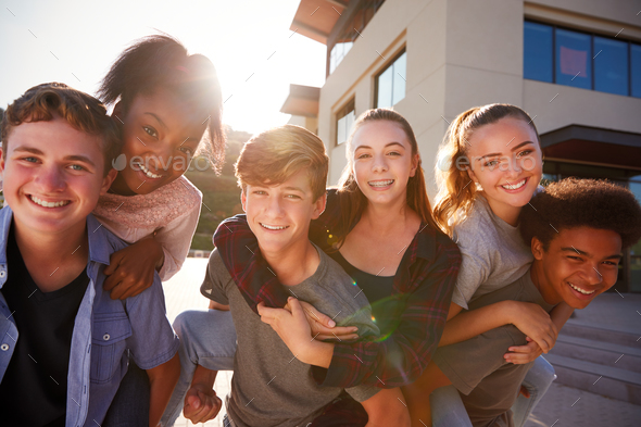 Portrait Of High School Students Giving Each Other Piggybacks College Buildings - Stock Photo - Images