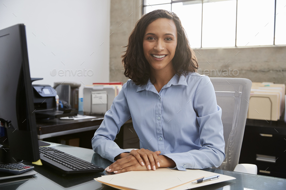 Young female professional sitting at desk in an office - Stock Photo - Images