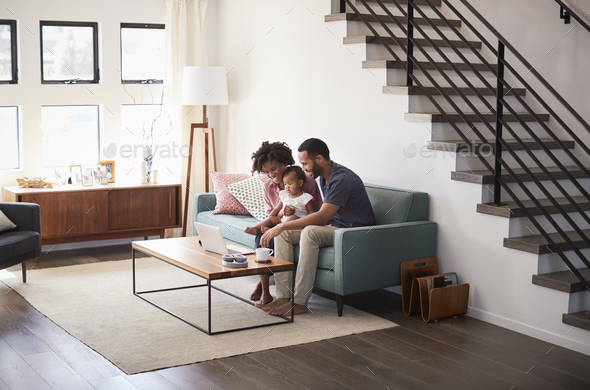 Family With Baby Daughter Sitting On Sofa At Home Looking At Laptop Computer - Stock Photo - Images