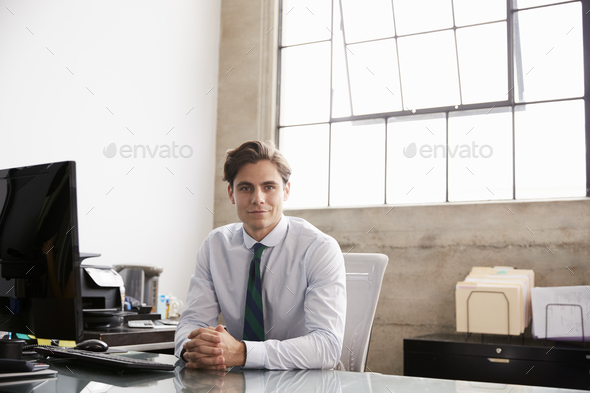 Young businessman sitting at office desk smiling to camera - Stock Photo - Images