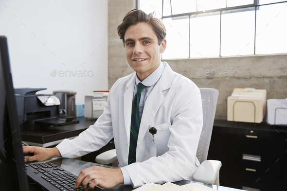 Young white male doctor using computer smiling to camera - Stock Photo - Images
