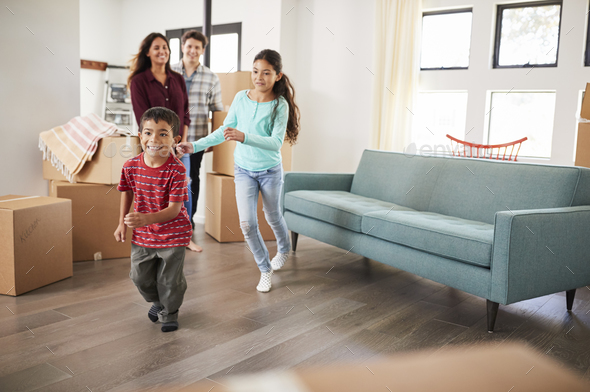 Excited Family Surrounded By Boxes Exploring New Home On Moving Day - Stock Photo - Images