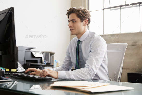 Young white businessman using a computer at an office desk - Stock Photo - Images