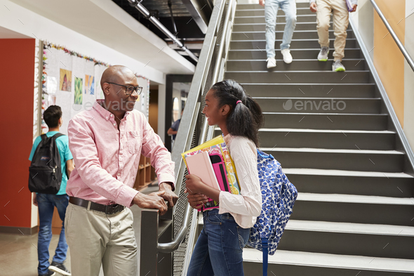 Female High School Student Talking With Teacher In Busy Corridor - Stock Photo - Images