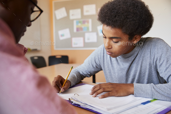 High School Tutor Giving Male Student One To One Tuition At Desk - Stock Photo - Images