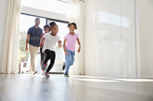Excited Family Exploring New Home On Moving Day - Stock Photo - Images