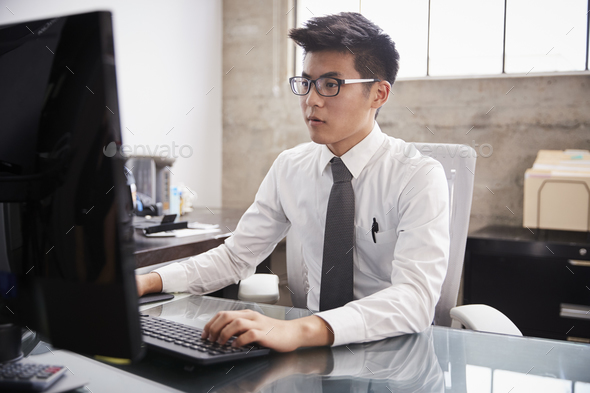 Young Asian businessman using a computer at an office desk - Stock Photo - Images