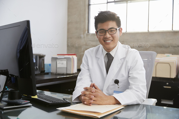 Young Asian male doctor sitting at desk, portrait - Stock Photo - Images