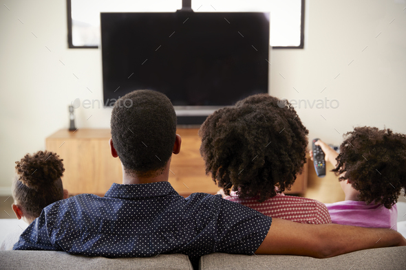 Rear View Of Family With Children Sitting On Sofa Watching TV Together - Stock Photo - Images